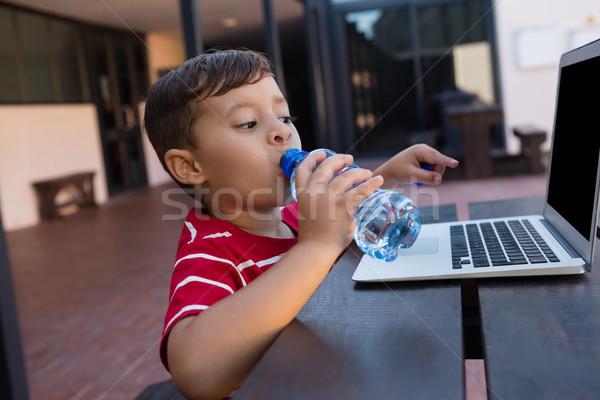 Stok fotoğraf: Erkek · içme · suyu · dizüstü · bilgisayar · kullanıyorsanız · tablo · okul · bilgisayar