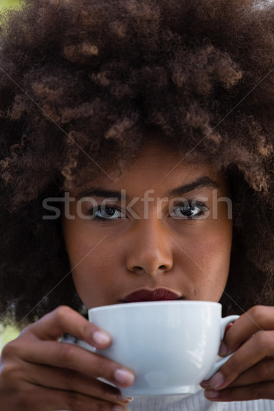 Portrait of young woman with frizzy hair holding coffee cup Stock photo © wavebreak_media