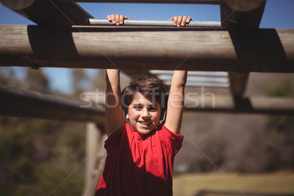 Portrait of happy boy exercising on monkey bar during obstacle course Stock photo © wavebreak_media
