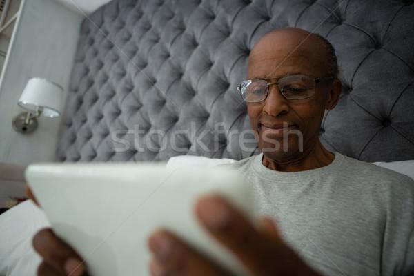 Senior man using digital tablet while relaxing on bed Stock photo © wavebreak_media