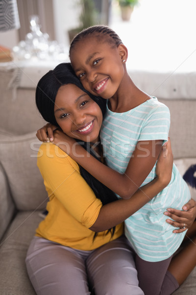 Smiling mother and daughter embracing on sofa at home Stock photo © wavebreak_media