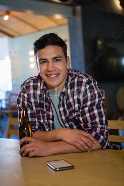 Portrait of smiling man holding beer bottle Stock photo © wavebreak_media