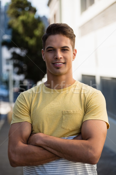 Handsome young man with arms crossed standing in city Stock photo © wavebreak_media