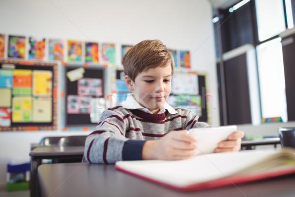 Boy using mobile phone at desk Stock photo © wavebreak_media