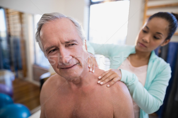 Shirtless male patient receiving neck massage from female therapist Stock photo © wavebreak_media