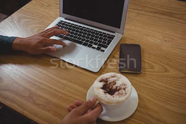 Cropped hands of man having coffee while using laptop in cafe Stock photo © wavebreak_media