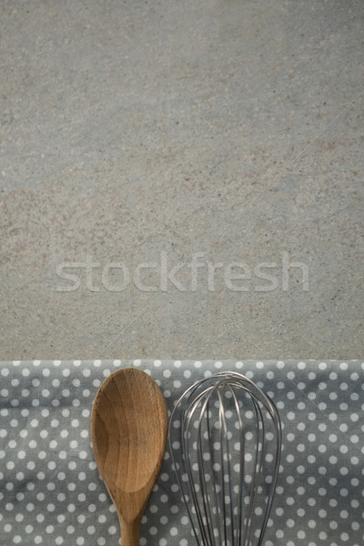 Cropped image of wooden spoon with wire whisk on napkin Stock photo © wavebreak_media