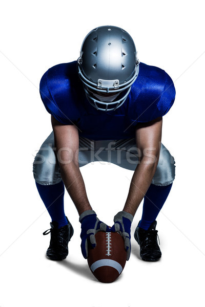 American football player in uniform holding ball while crouching Stock photo © wavebreak_media