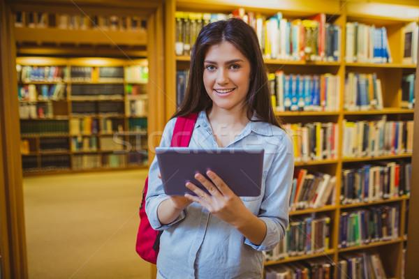 Morena estudante comprimido prateleiras para livros biblioteca mulher Foto stock © wavebreak_media