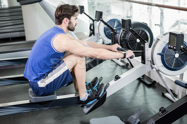 Handsome man doing exercise on drawing machine Stock photo © wavebreak_media