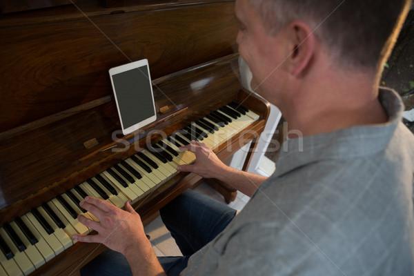 Stock photo: Man playing piano at home