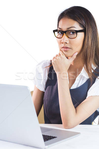 Thoughtful businesswoman using laptop and holding her chin Stock photo © wavebreak_media