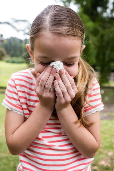 Sick girl sneezing in the park Stock photo © wavebreak_media