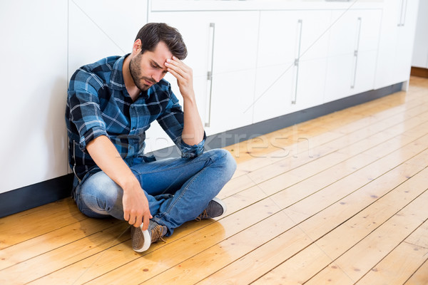 Tensed man with hand on forehead sitting on wooden floor Stock photo © wavebreak_media
