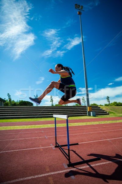 Female athlete jumping above the hurdle Stock photo © wavebreak_media