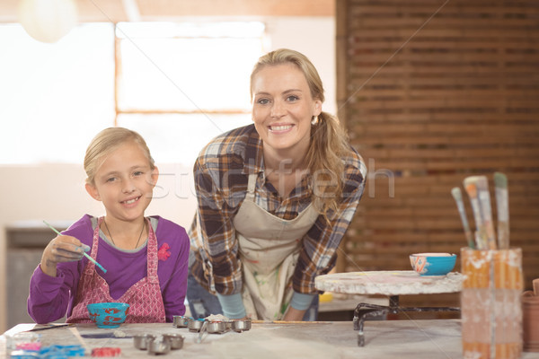Smiling female potter and girl painting in pottery workshop Stock photo © wavebreak_media