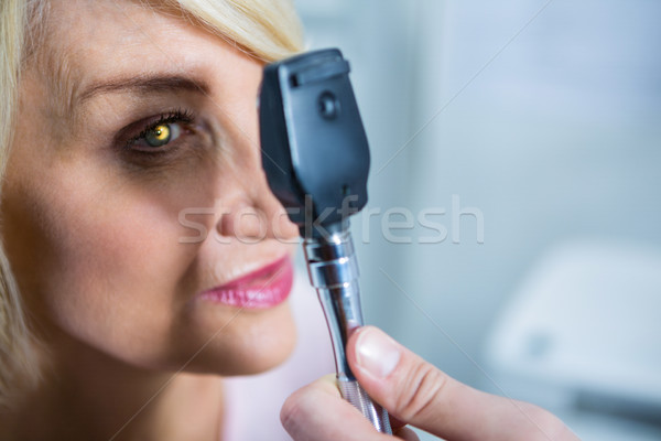Optometrist examining female patient through ophthalmoscope Stock photo © wavebreak_media