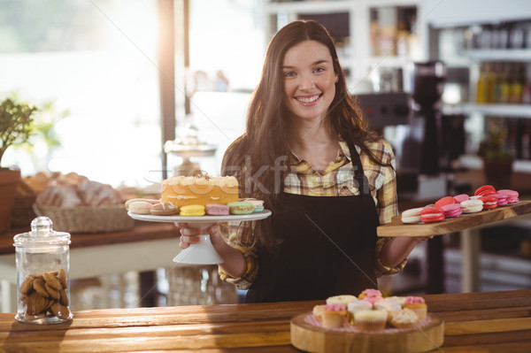 Portrait of waitress standing at counter with desserts Stock photo © wavebreak_media