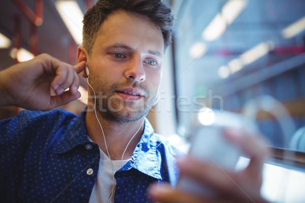Jóképű férfi hallgat zene mobiltelefon vonat szeretet Stock fotó © wavebreak_media