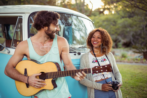 Man playing guitar near campervan while woman standing beside him Stock photo © wavebreak_media