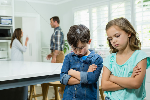 Sad siblings standing with arms crossed while parents arguing in background Stock photo © wavebreak_media