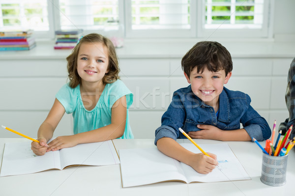 Portrait of smiling siblings studying together in living room Stock photo © wavebreak_media