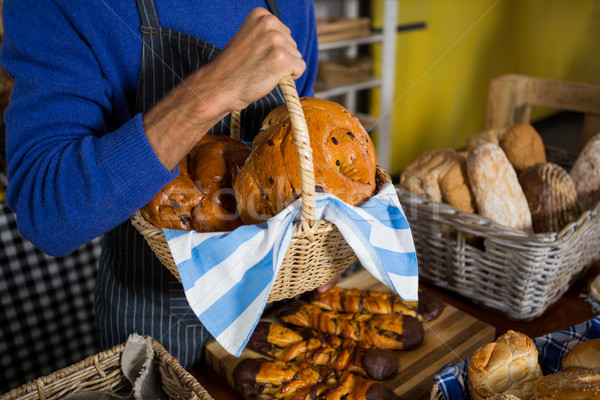 Mid section of staff holding wicker basket of breads at counter Stock photo © wavebreak_media