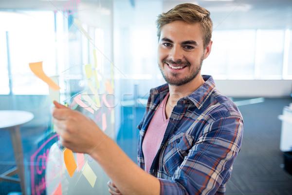 Sorridente homem tocante nota pegajosa vidro parede Foto stock © wavebreak_media