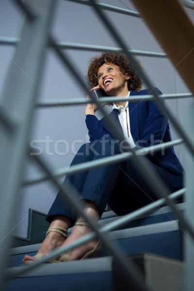 Kobieta interesu mówić telefonu komórkowego posiedzenia kroki kobieta Zdjęcia stock © wavebreak_media