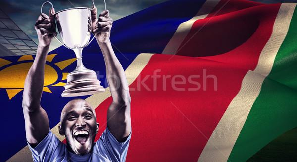 Composite image of happy athlete cheering while holding trophy Stock photo © wavebreak_media