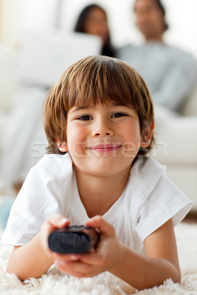 Adorable little boy watching TV lying on the floor  Stock photo © wavebreak_media