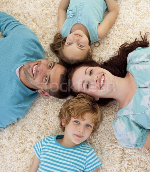 Happy family on floor with heads together Stock photo © wavebreak_media