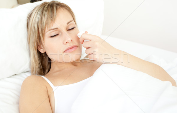Portrait of a sick beautiful woman lying on a bed Stock photo © wavebreak_media