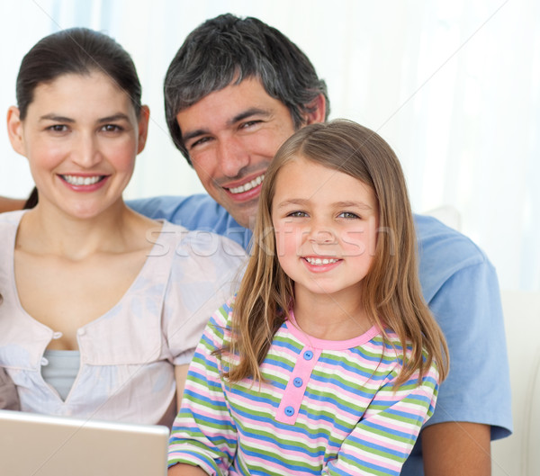 Little girl using a laptop with her parents on the sofa Stock photo © wavebreak_media
