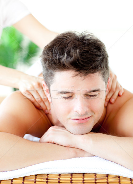 Stock photo: Portrait of a handsome man having a back massage in a spa center