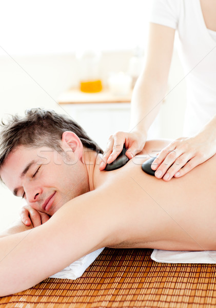 Stock photo: Happy young man enjoying a back massage with hot stone in a spa center