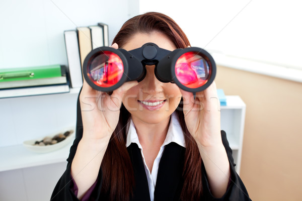 Radiant businesswoman sitting on a chair and looking through binoculars in her office Stock photo © wavebreak_media