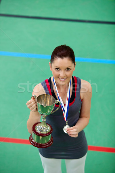 Stock photo: Smiling young woman holding a trophee and a medal in a gymnasium