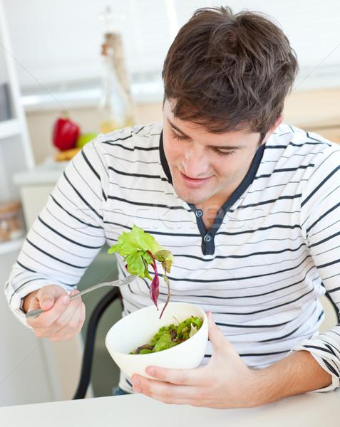 Encantado moço alimentação saudável salada cozinha casa Foto stock © wavebreak_media