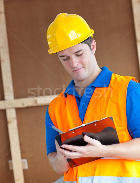 Jóképű munkás munkavédelmi sisak jegyzetel vágólap munka Stock fotó © wavebreak_media