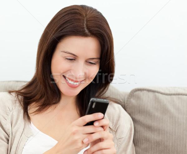 Lettura sms cellulare divano donna Foto d'archivio © wavebreak_media