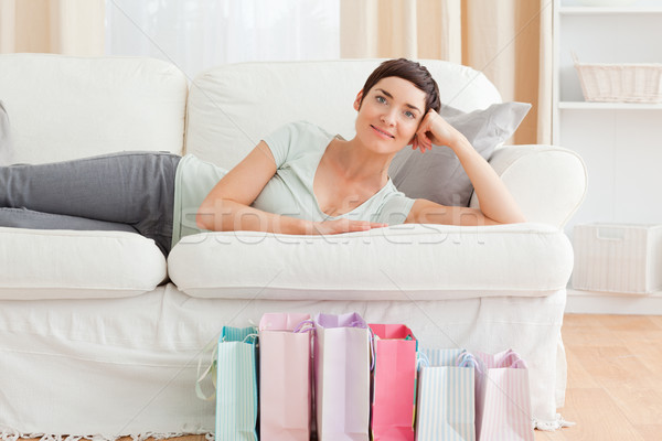 Stock photo: Smiling woman with shopping bags in her living room