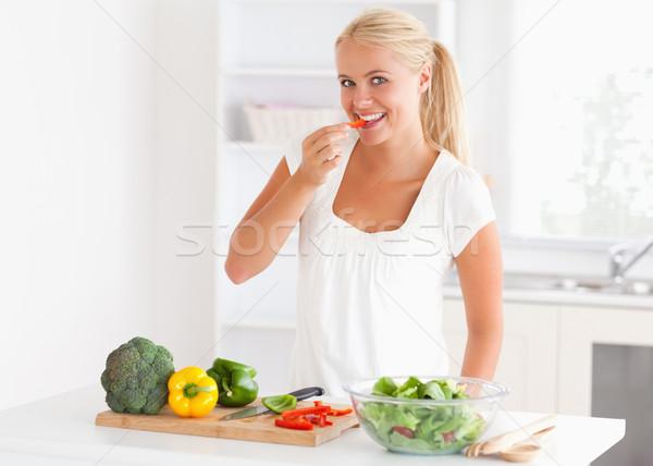 Woman eating pepper in her kitchen Stock photo © wavebreak_media