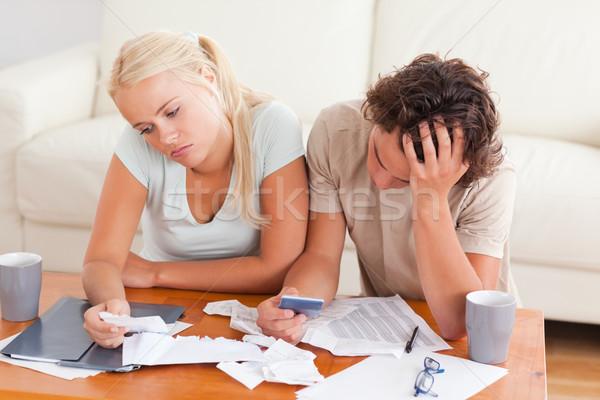 Unhappy couple listing expenses in the living room Stock photo © wavebreak_media