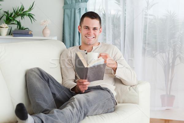 Heureux homme lecture livre salon maison Photo stock © wavebreak_media
