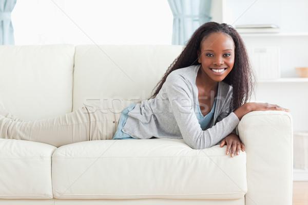 Smiling woman lying on the sofa Stock photo © wavebreak_media