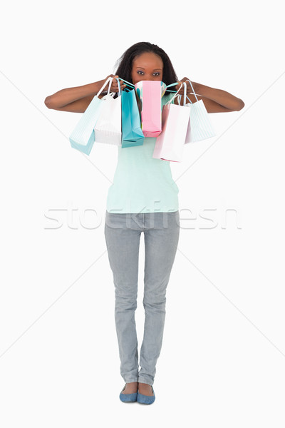 Young woman hiding behind her shopping on white background Stock photo © wavebreak_media