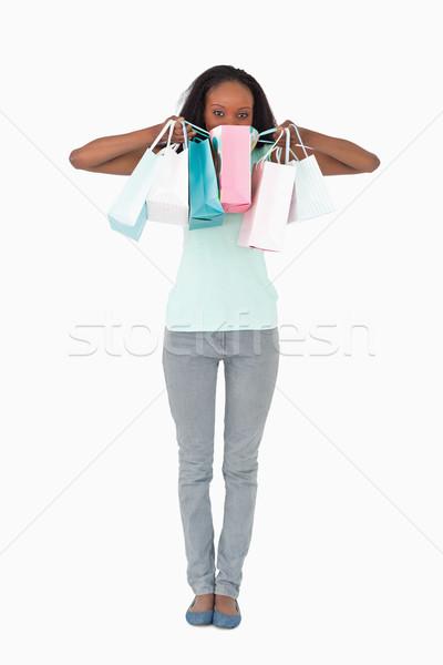 Jeune femme cacher derrière Shopping blanche mode Photo stock © wavebreak_media