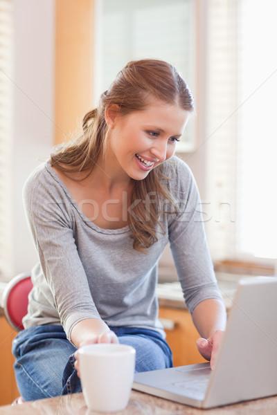 Fiatal nő kávé szörfözik háló laptop konyha Stock fotó © wavebreak_media