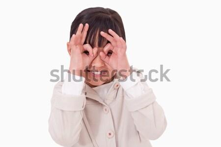 Girl putting her fingers around her eyes against a white background Stock photo © wavebreak_media
